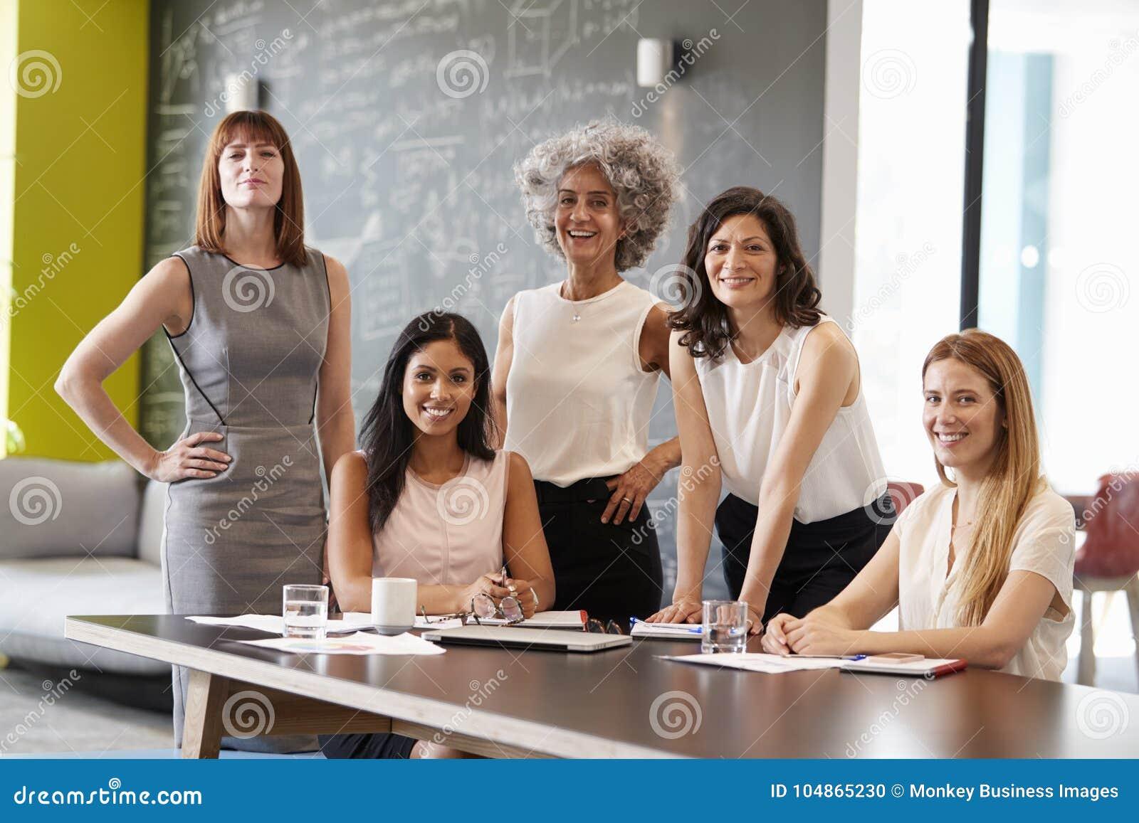 Vijf vrouwelijke collega s op een het werkvergadering die aan camera glimlachen