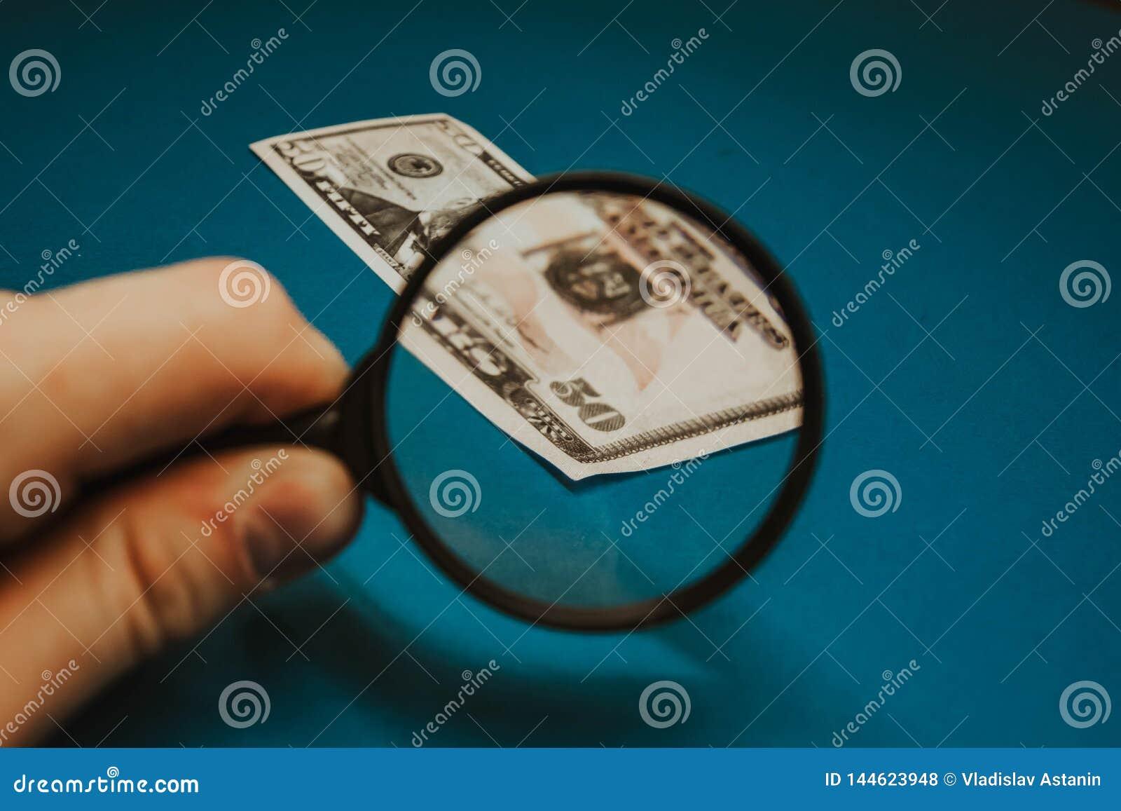 Vijftig dollarrekening op een blauwe achtergrond die door een vergrootglas worden bestudeerd
