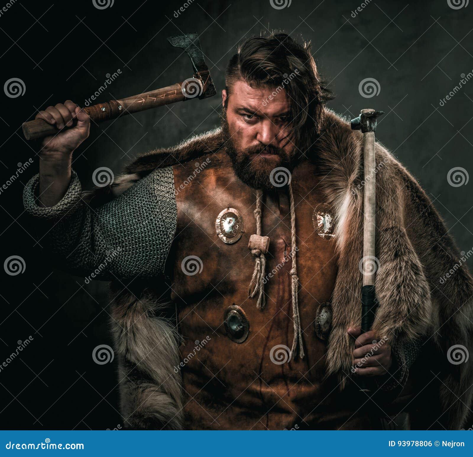 Viking con el arma fría en un guerrero tradicional viste
