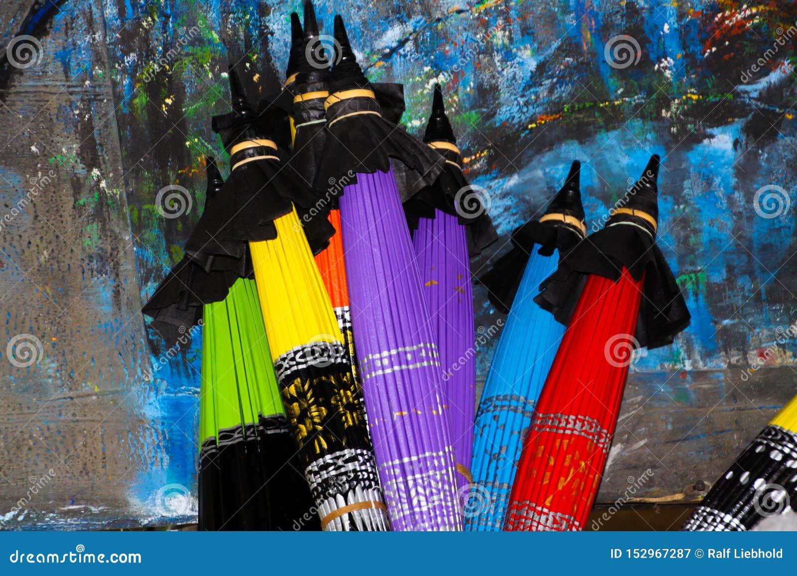 Vikta färgrika pappers- paraplyer som lutar på en målad vägg i Chiang Mai, Thailand