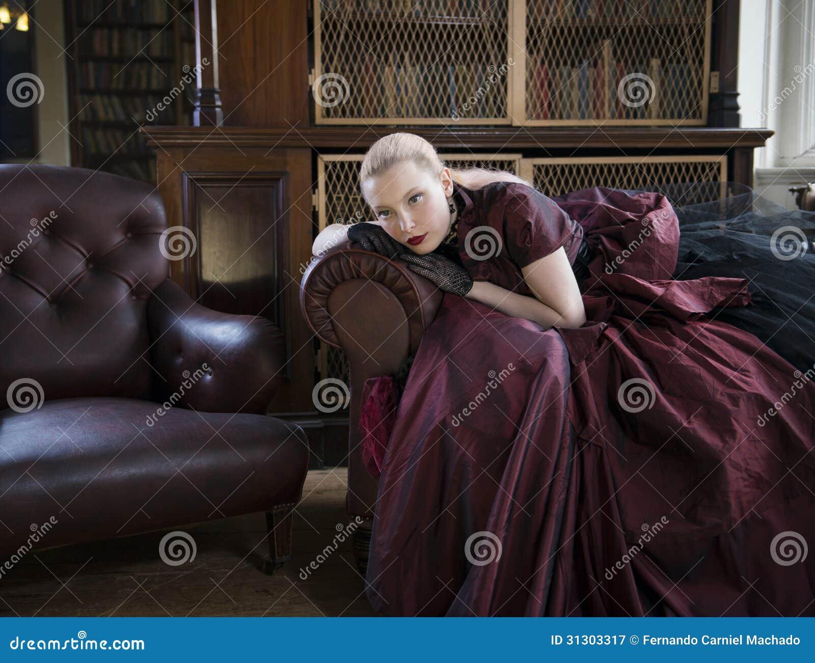 6cf50110 Härlig caucasian kvinna i den röda viktorianska klänningen som väntar i  gammalt arkiv