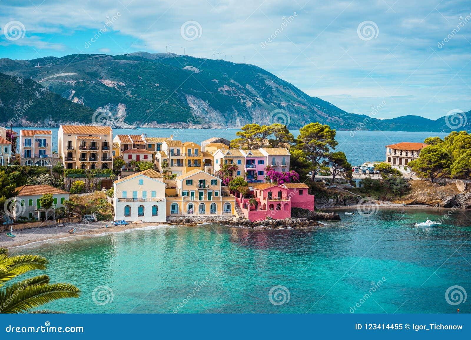 Vila de Assos A vista bonita às casas coloridas vívidas perto da turquesa azul coloriu a lagoa transparente da baía Kefalonia