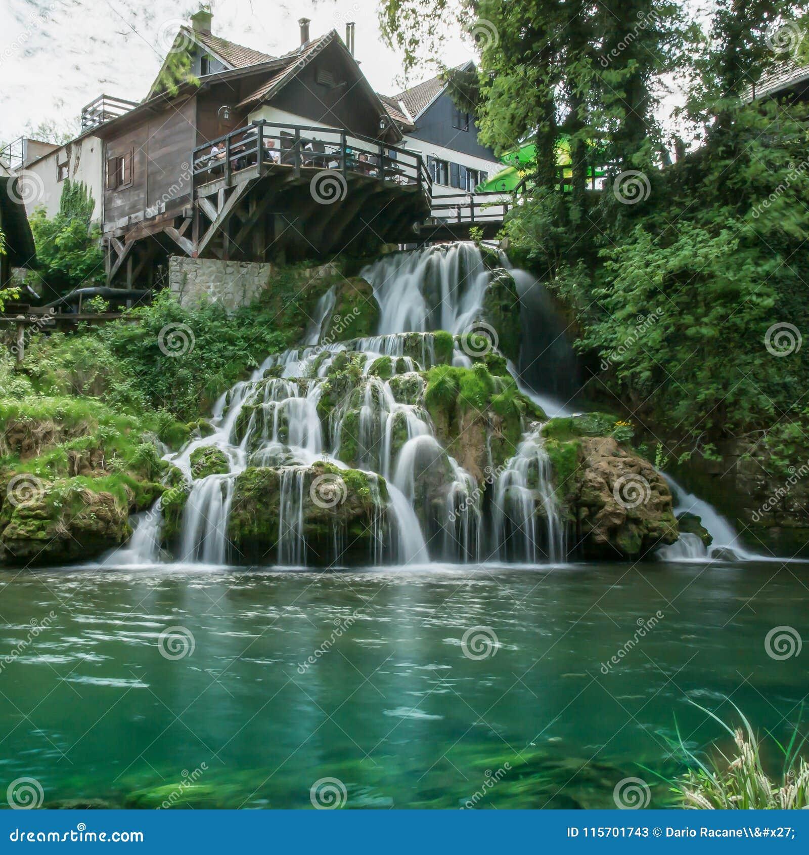 Vila de Rastoke por um rio de Korana com casas de madeira e uma cachoeira, Croácia