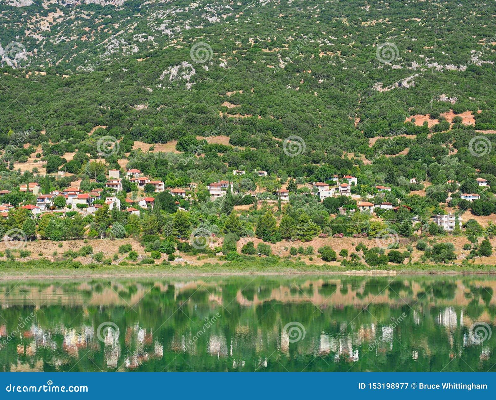 Vila grega da montanha refletida na água do lago
