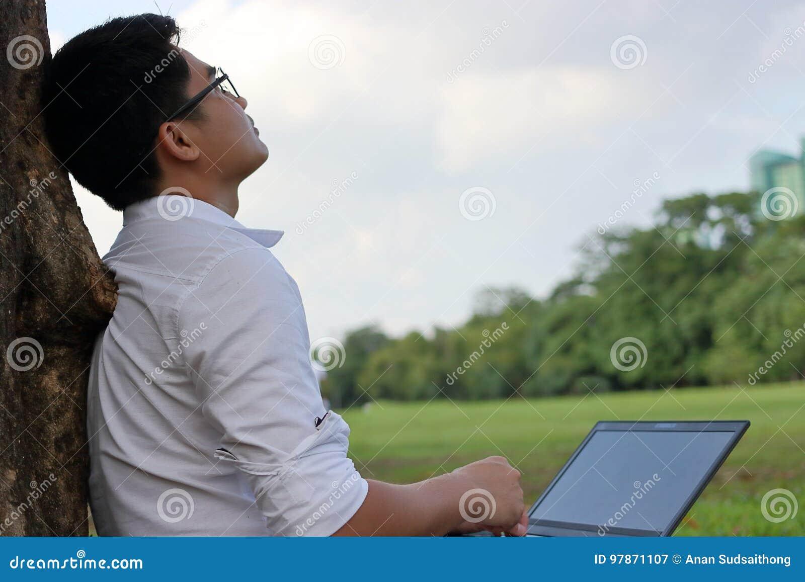 Vila tid Asiatisk ung man som ser himlen efter arbete mot hans bärbar dator