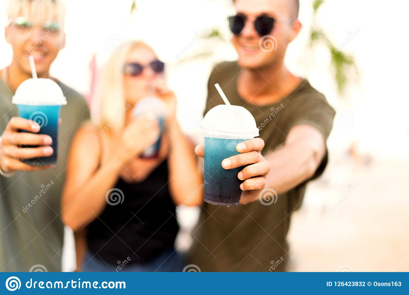 Vilar det gladlynta företaget för tre vänner på en tropisk strand och drin