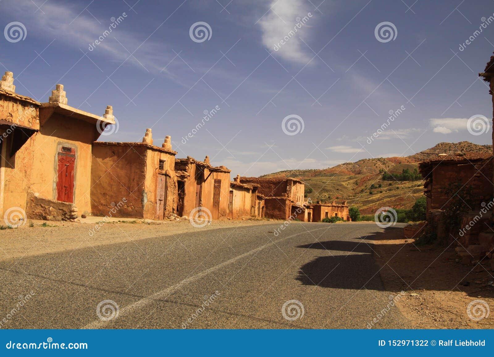 Village abandonné des maisons d argile le long de route vide en montagnes d atlas, Maroc