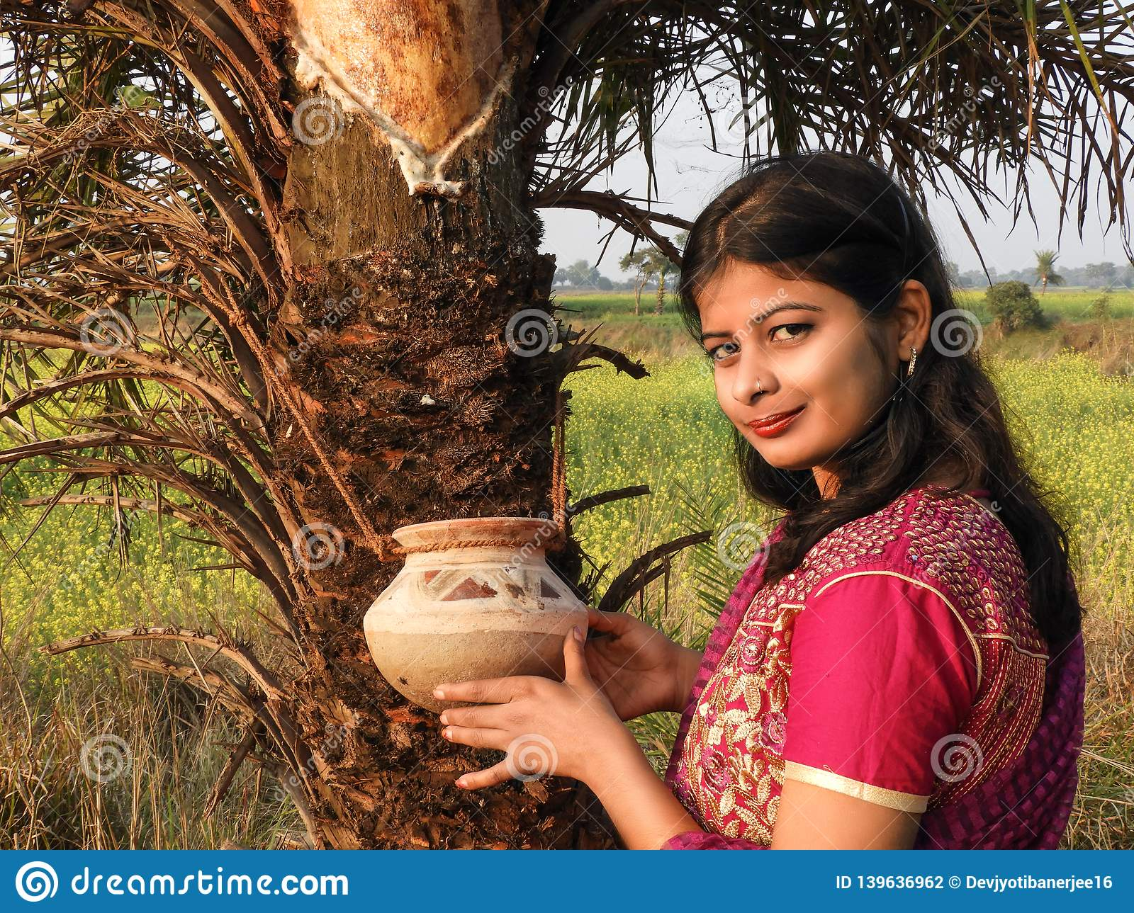 A village girl stood at the front of date tree, spring time