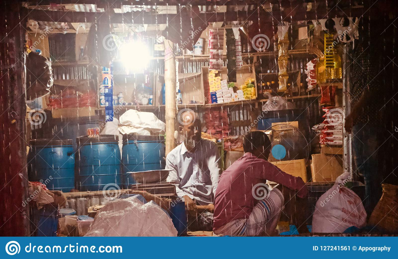 Village shopkeeper sitting in a shop in a rainy nights unique photo
