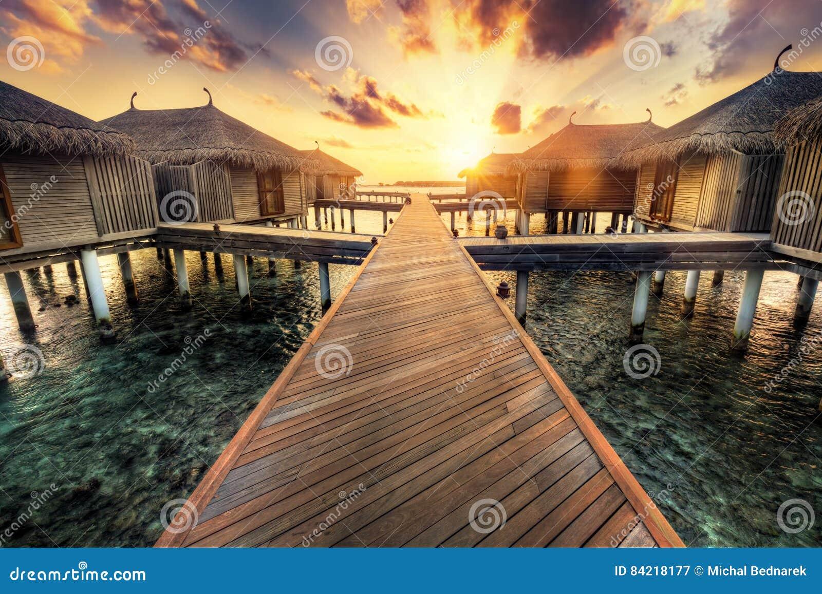 Villas en bois de jetée et d eau Île-hôtel des Maldives au coucher du soleil