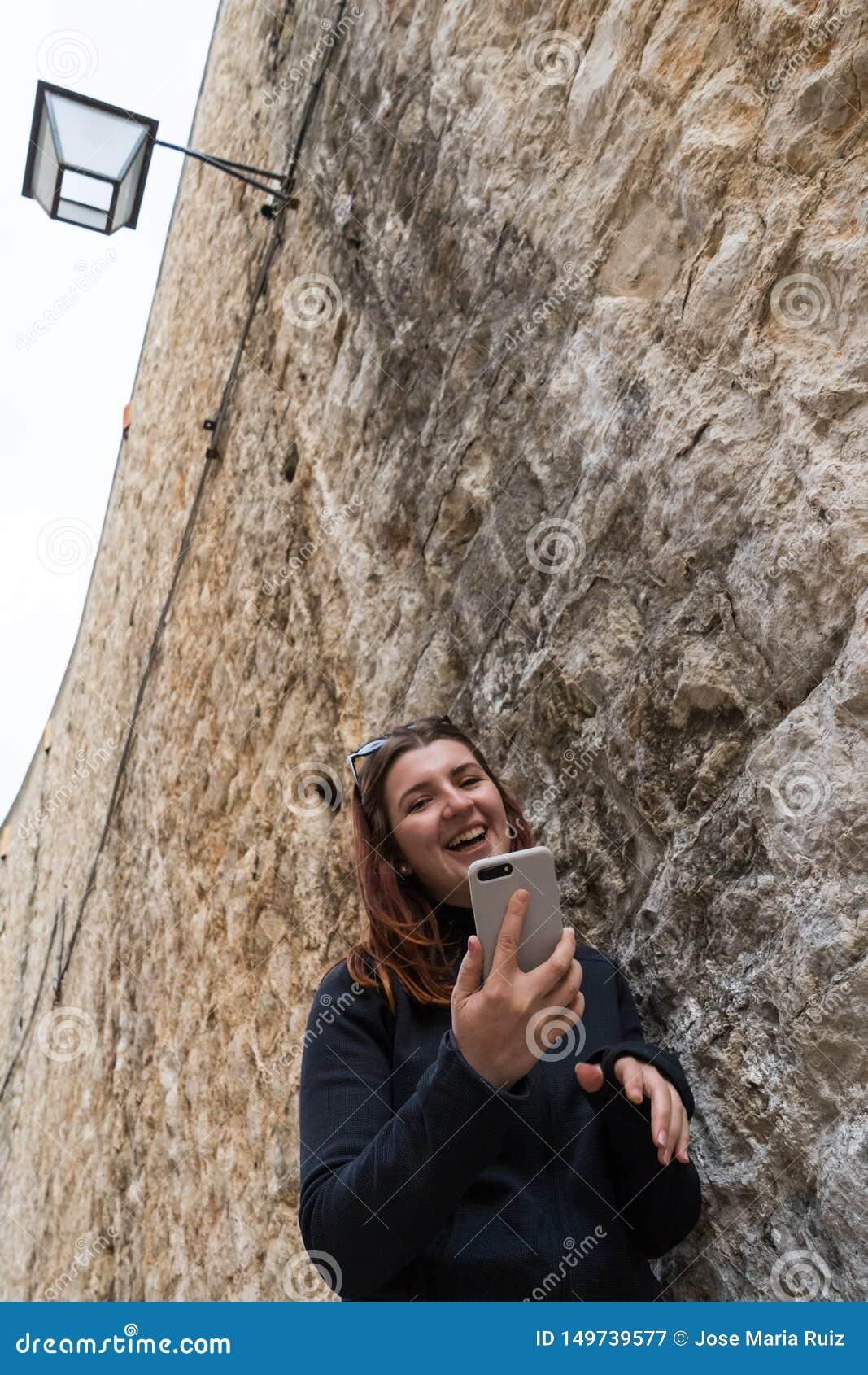 Ville de visite de belle jeune femme de touristes visitant le pays sur le mur en pierre, tenant le smartphone prenant des photos