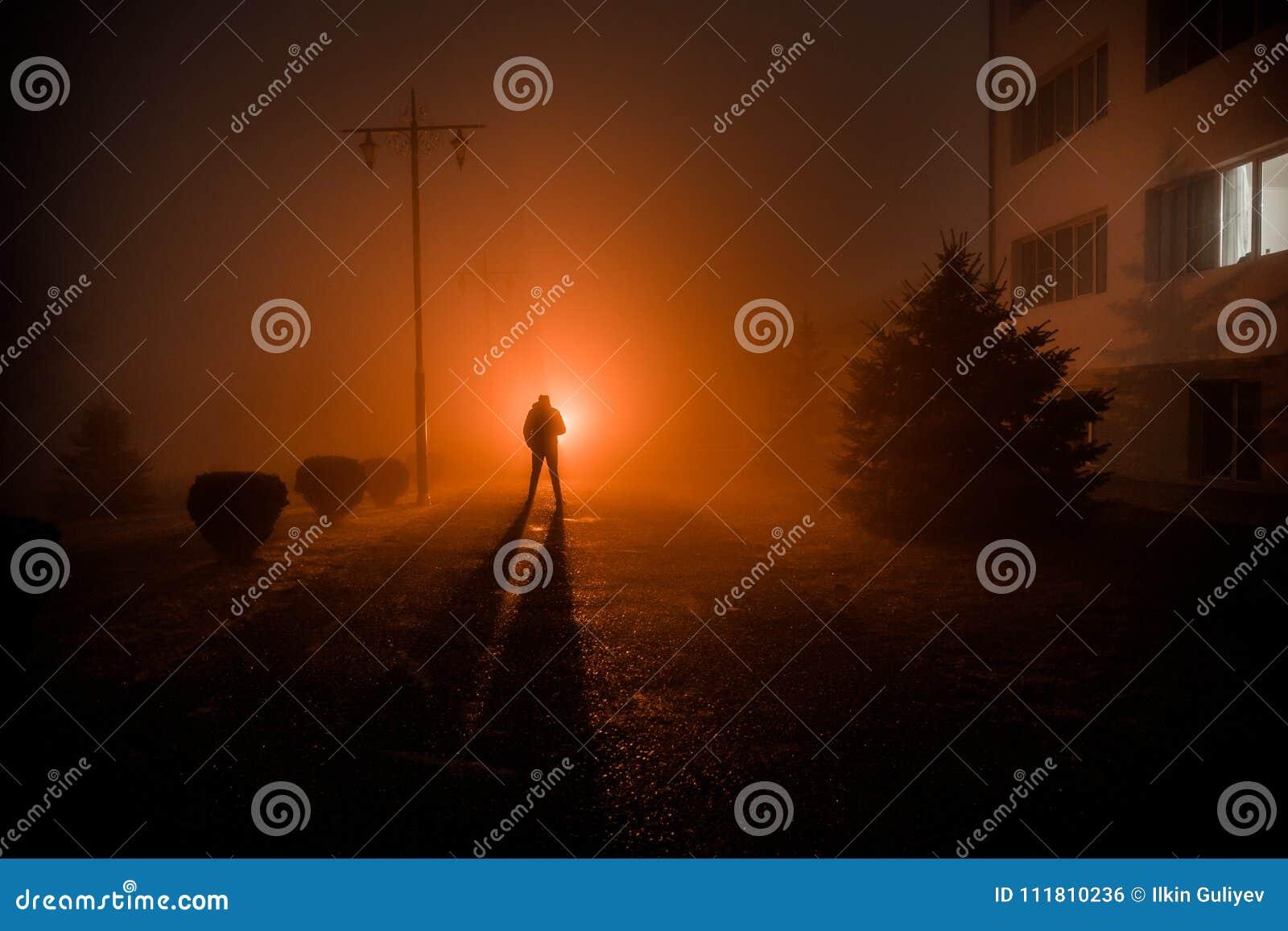 Ville la nuit en brouillard dense Lumières surréalistes de paysage mystique avec l homme rampant La silhouette de l homme de marc
