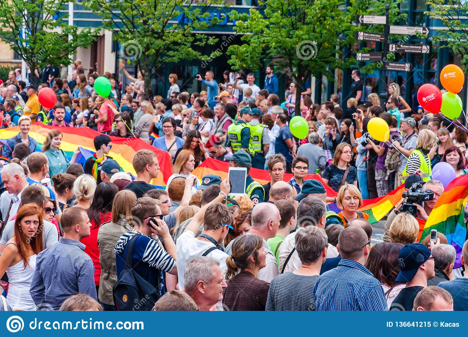 Pride parade in action. Crowd of watchers and demonstrators with rainbow flags. Event celebrating lesbian, gay, bisexual,