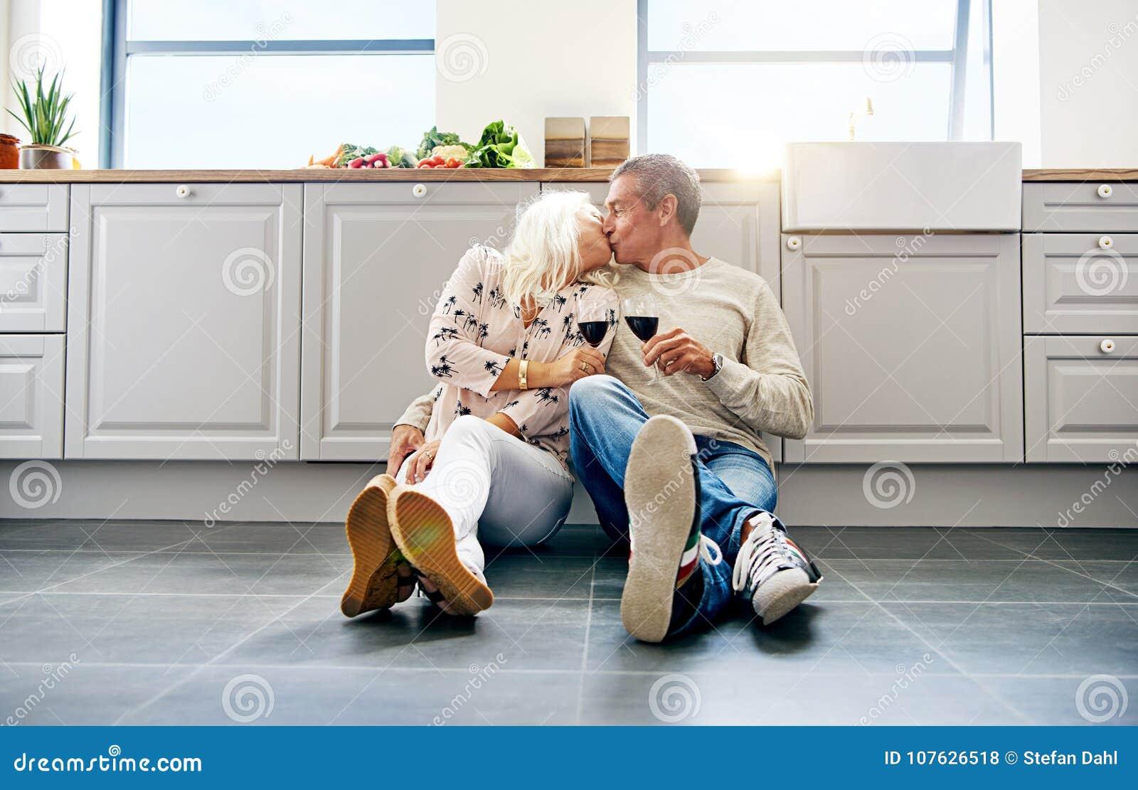 Vin de baiser et potable de couples supérieurs dans leur cuisine