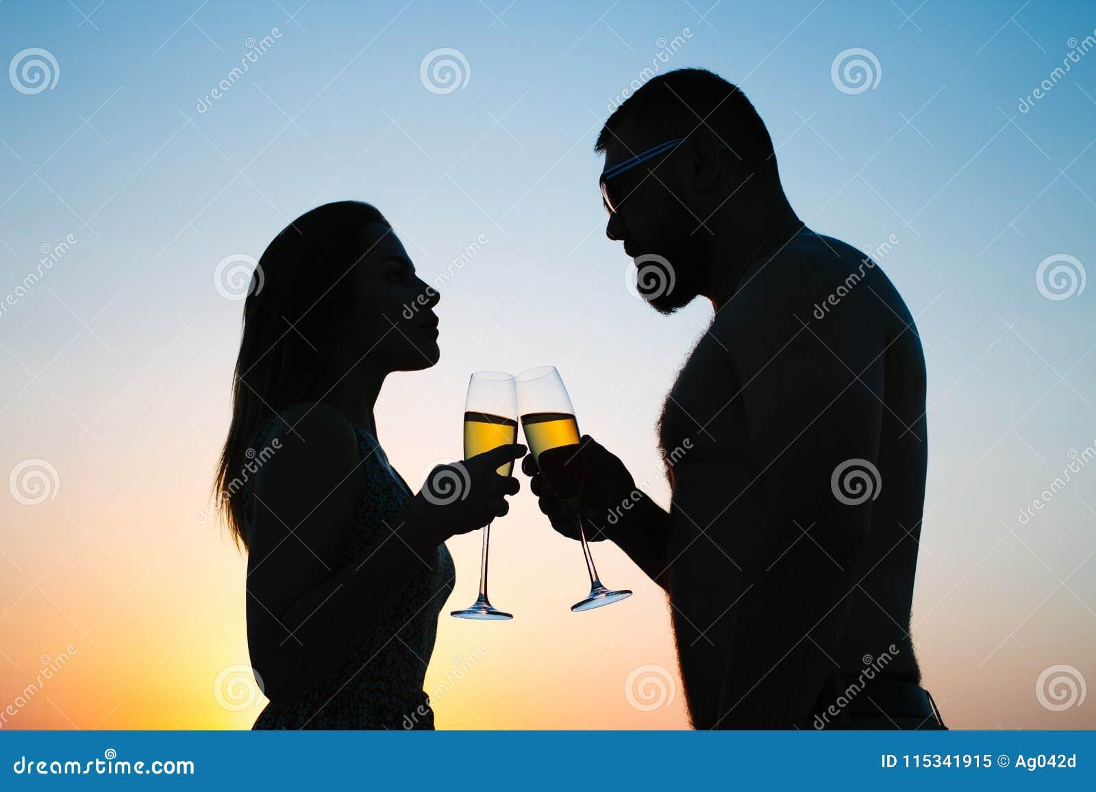 Vin de couples affectueux ou champagne potable pendant le temps de coucher du soleil, silhouette d un ajouter aux verres à vin su
