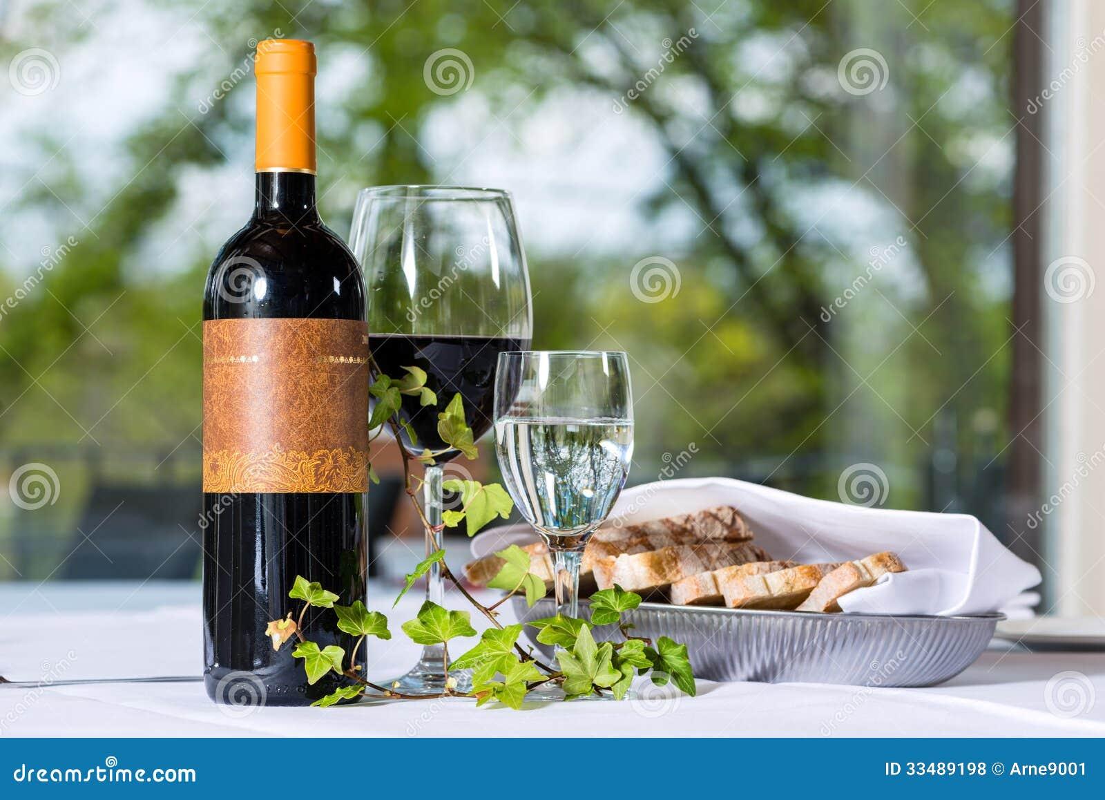 Vin rouge avec la bouteille et le verre sur une table for Ordre des verres sur la table