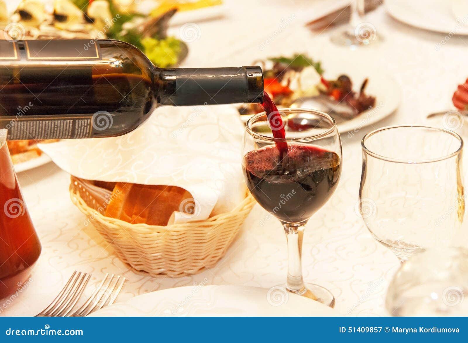 Vin rouge versant dans un verre de vin cette position sur for Position verre sur table