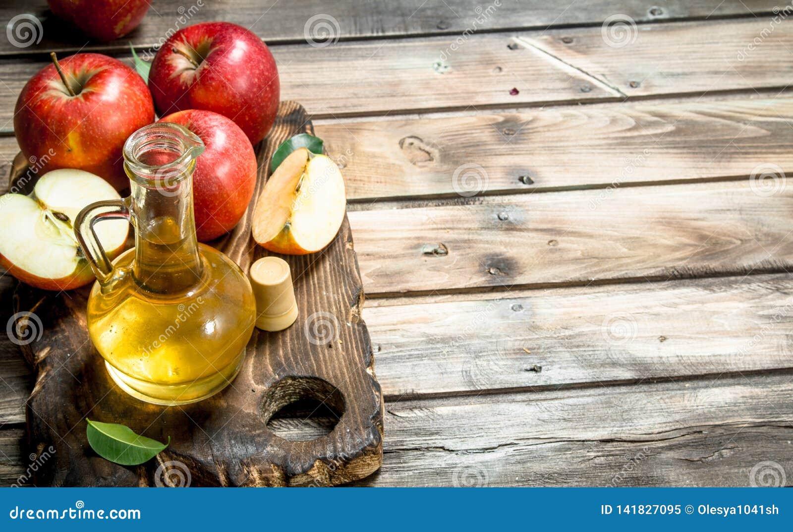 Vinagre de sidra de Apple con las manzanas rojas frescas en una tabla de cortar