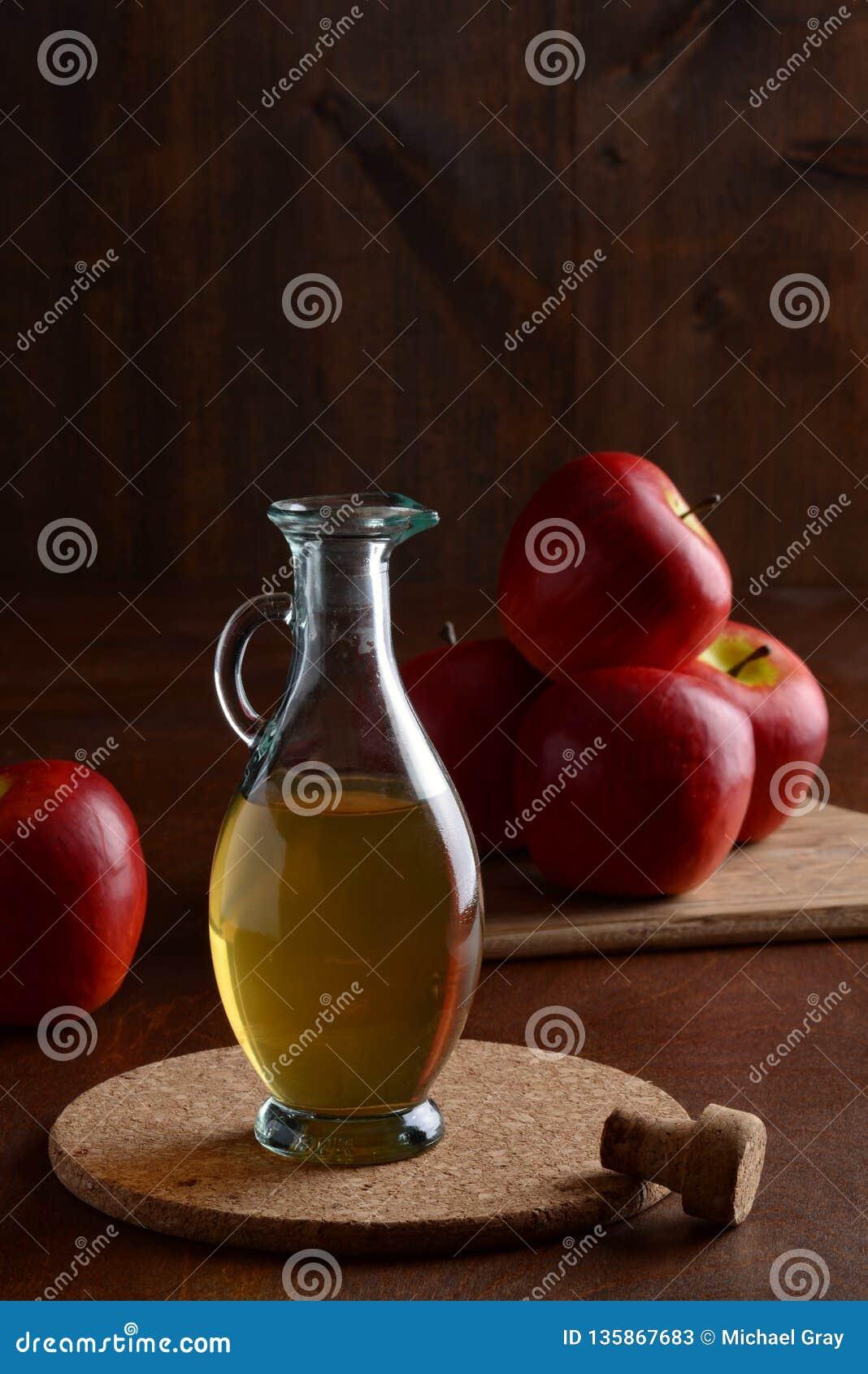 Vinaigre de cidre de pomme de plan rapproché sur le tapis de liège