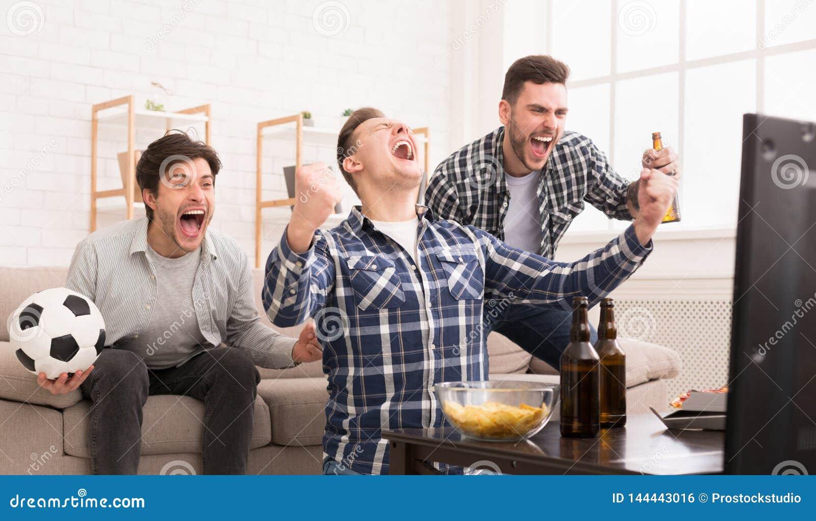 Vincitori Amici emozionanti che guardano calcio a casa