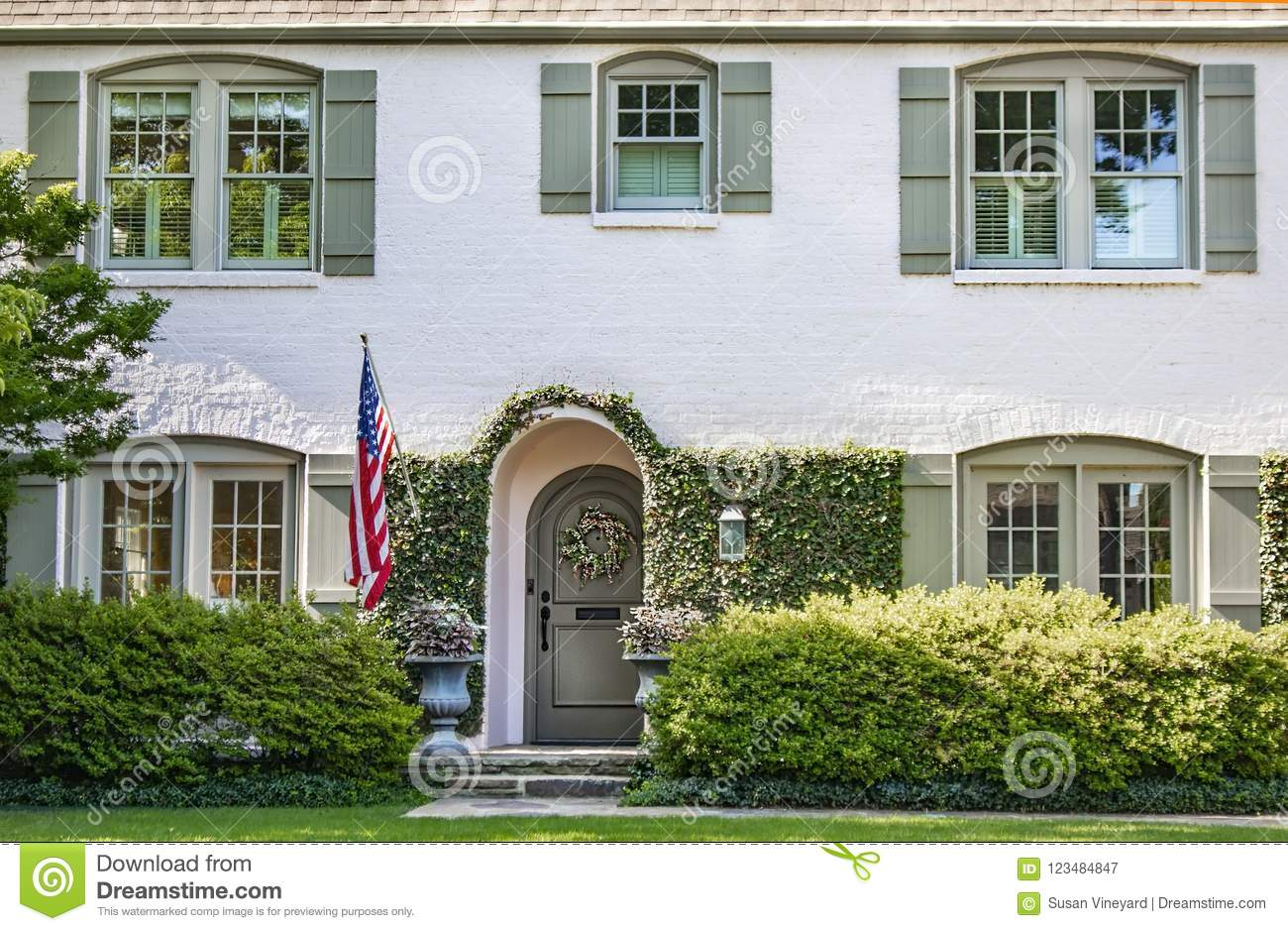 Vine Covered Entrance To White Painted Brick House With Arched Front