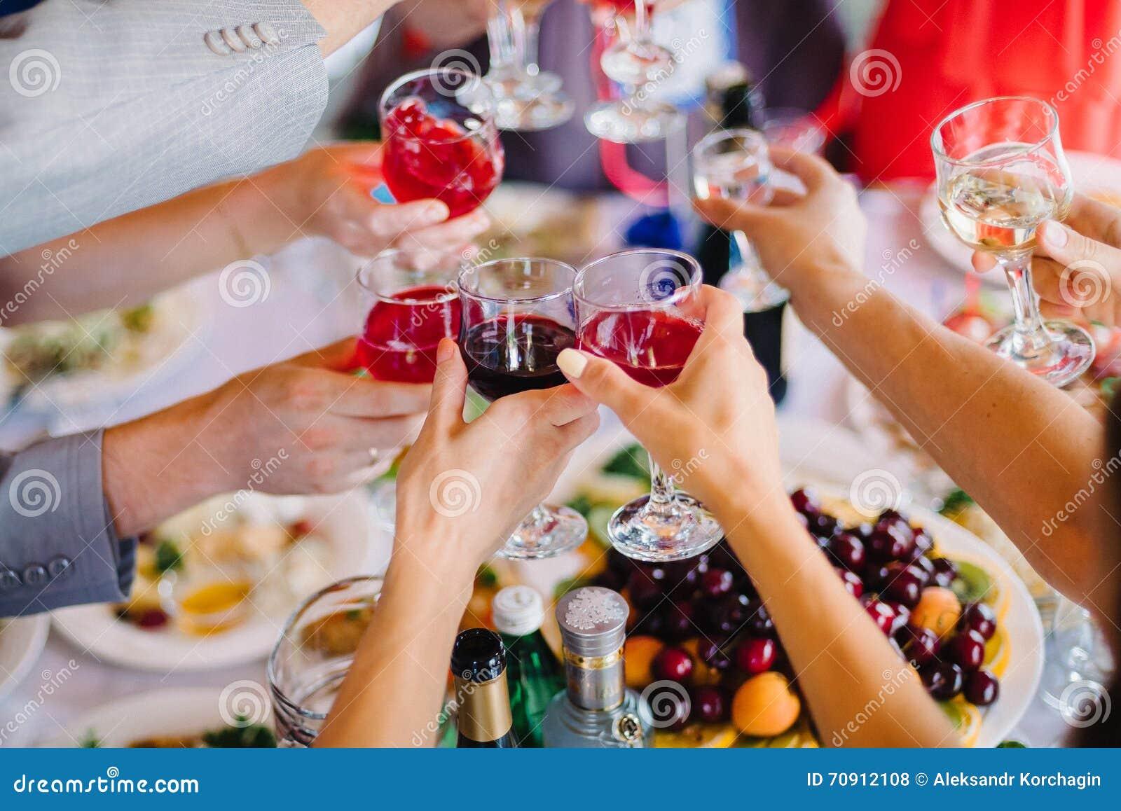 Vinexponeringsglas i handgrupp människor för lyckligt parti