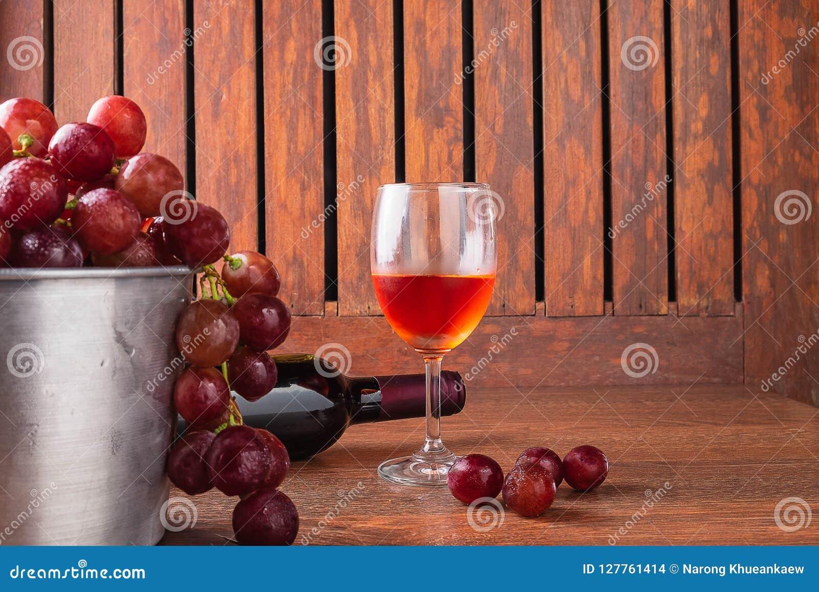 Vinexponeringsglas och vinflaska med röda druvor på träbakgrund