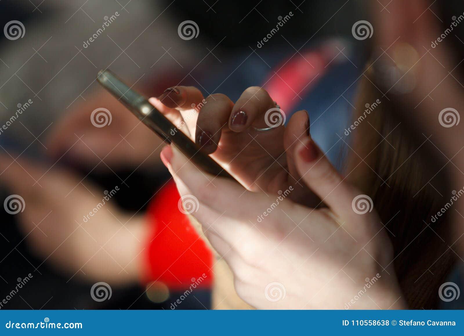 Vingers die op een cellulaire telefoonvertoning typen