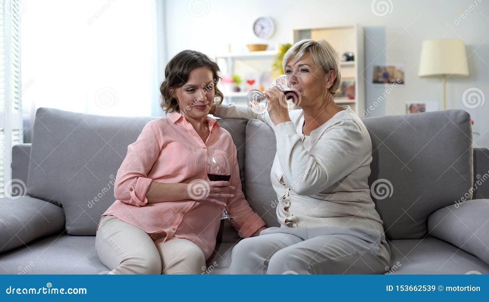 Vinho bebendo de conversa de sorriso da mãe e da filha em casa, relações macias