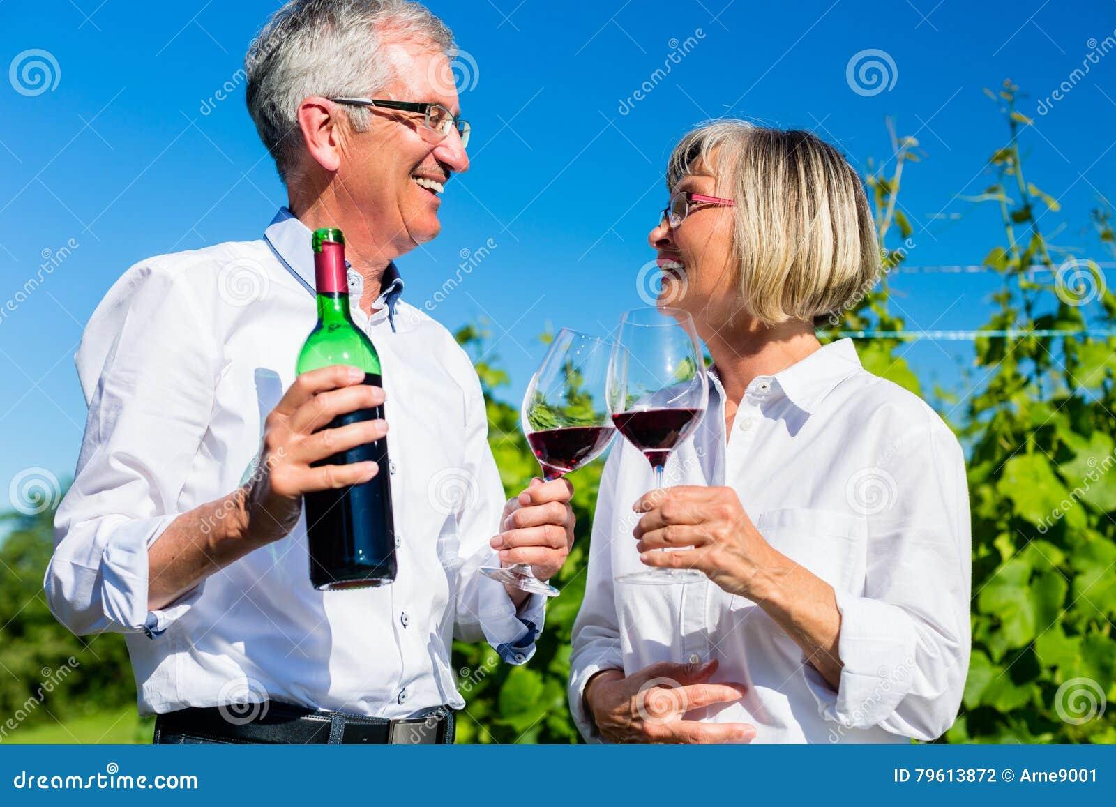 Vinho bebendo superior da mulher e do homem no vinhedo