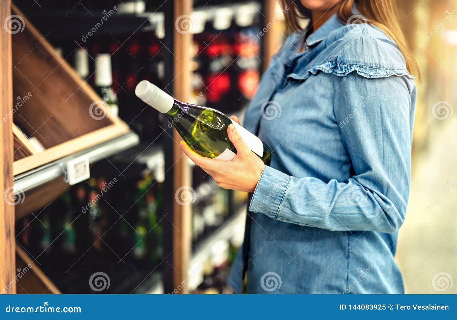 Vinho branco de compra do cliente ou bebida efervescente Corredor do álcool na loja ou no supermercado Garrafa da terra arrendada