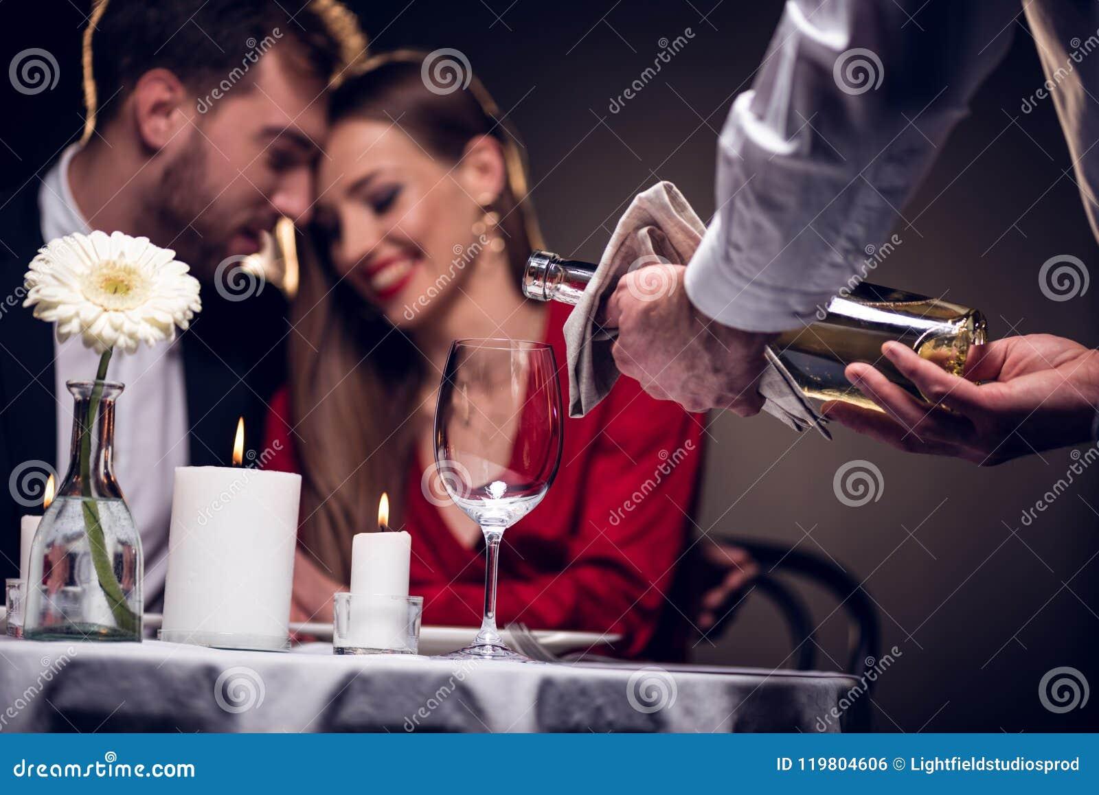 Vinho de derramamento do garçom quando pares bonitos que têm a data romântica no restaurante