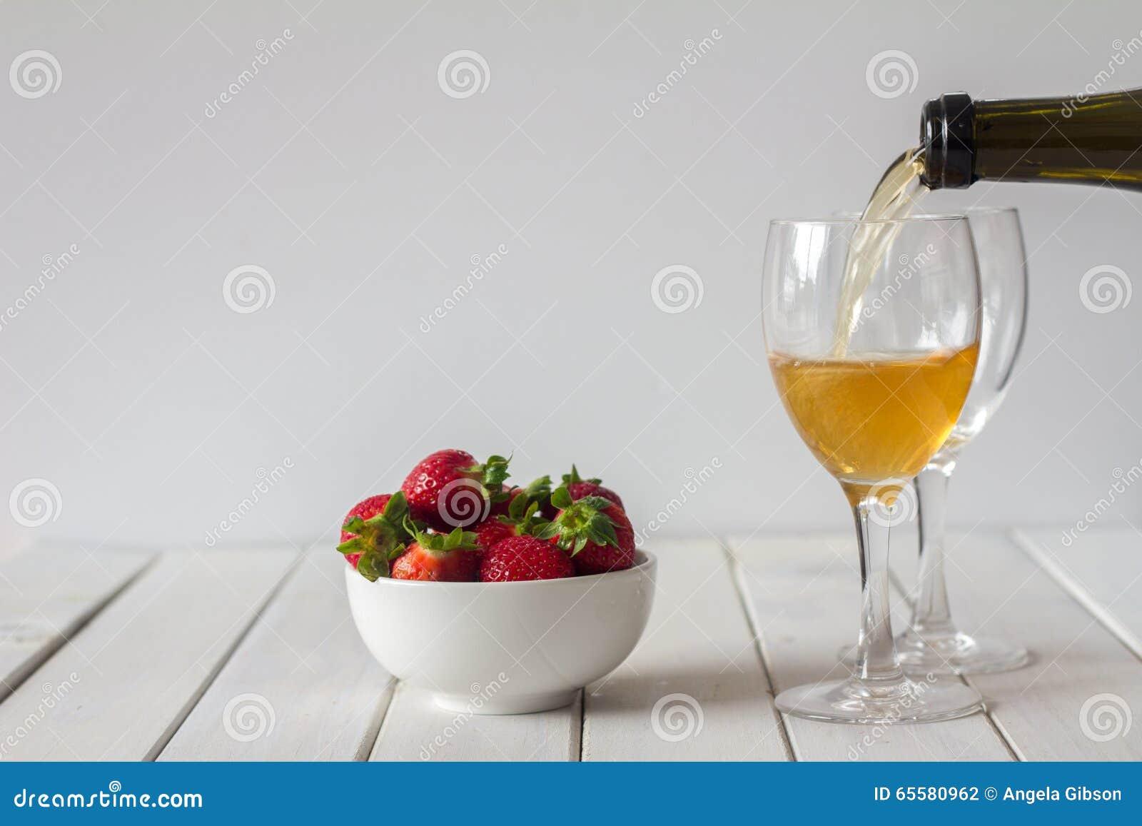Vinho e morangos de derramamento na tabela com espaço da cópia