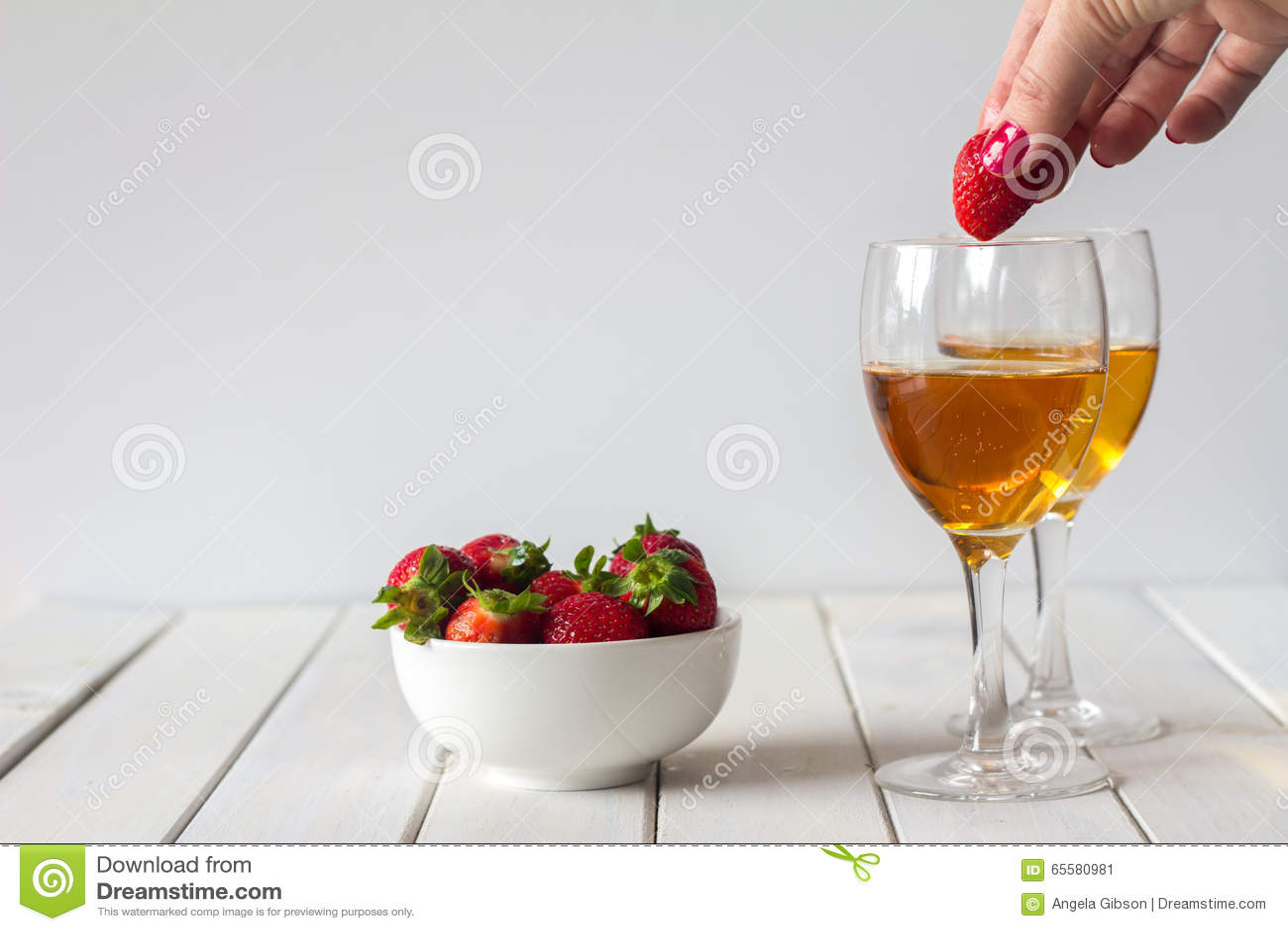 Vinho e morangos deixando cair no vidro na tabela com espaço da cópia