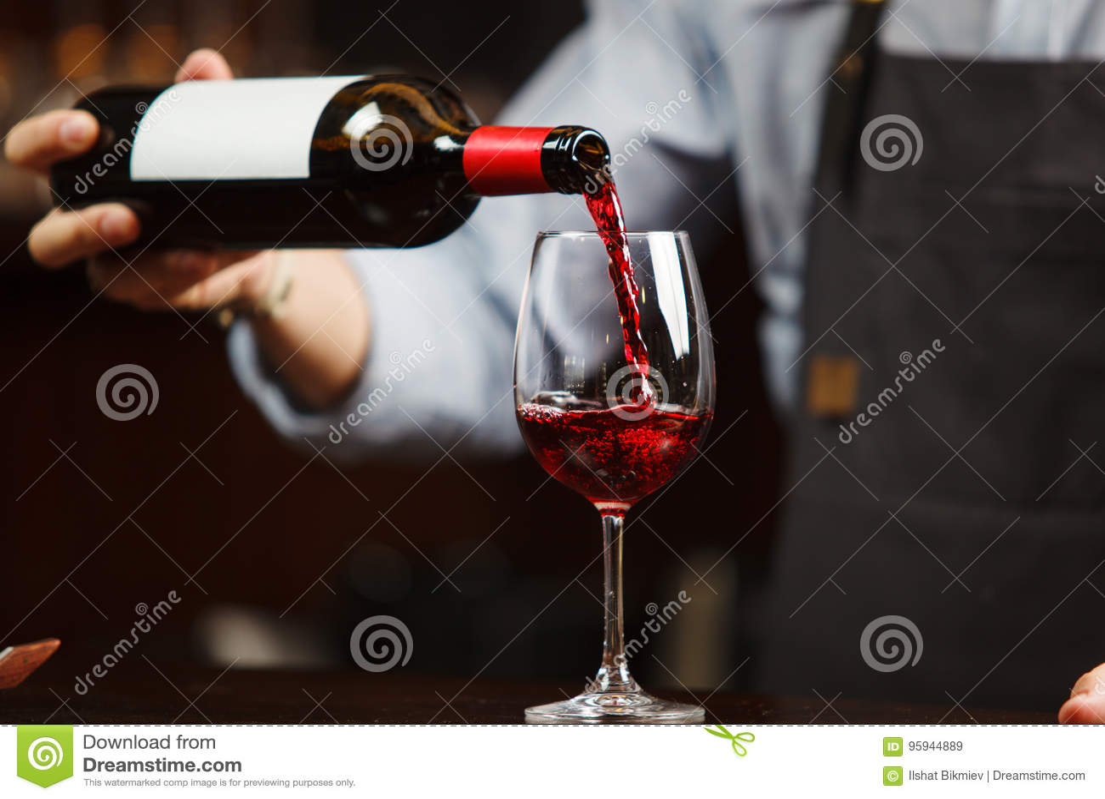 Vinho tinto de derramamento do garçom no copo de vinho O Sommelier derrama a bebida alcoólica
