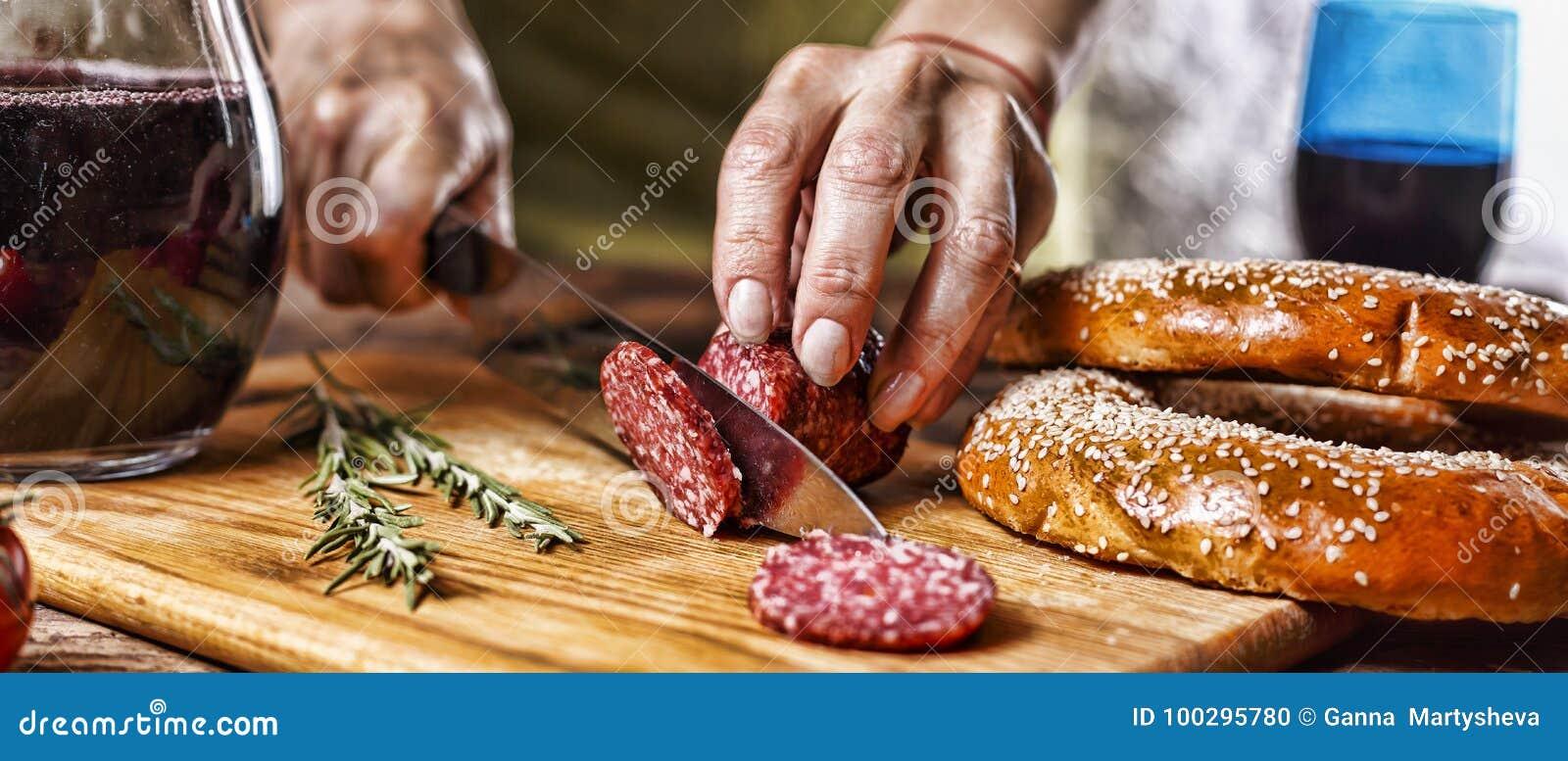 Vinho tinto italiano tradicional, salame, alecrim, pão O fim acima de uma mão do ` s da pessoa cortou o salame em uma placa da co