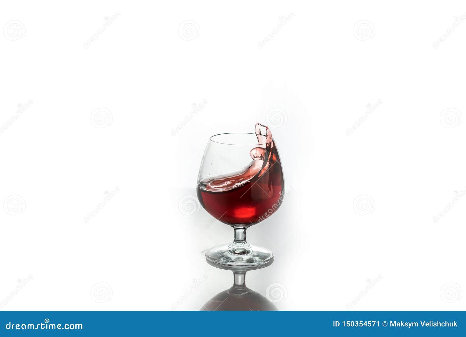 Vinho tinto que espirra fora de um vidro, isolado no branco