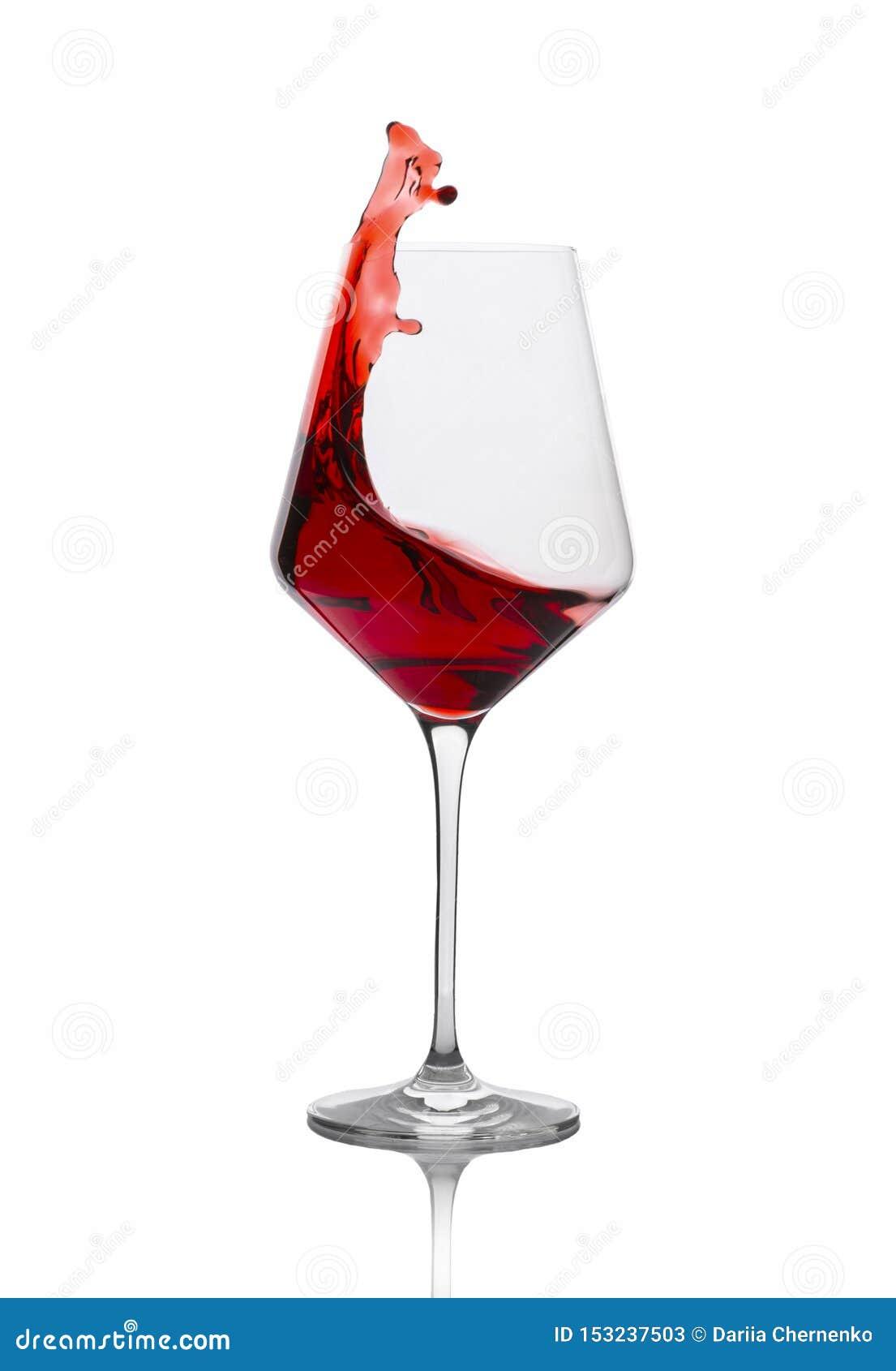 Vinho tinto que espirra fora de um vidro isolado no branco