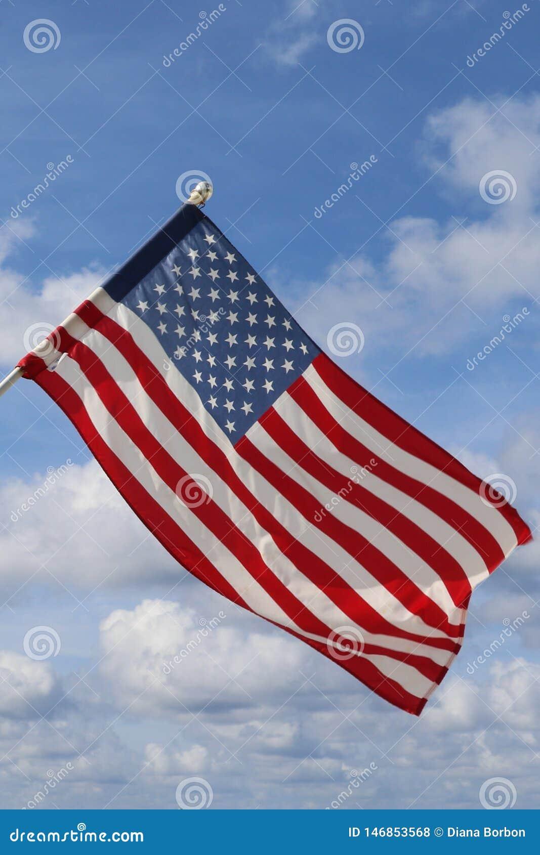 Vinkande USA flagga i bl? och molnig himmel Amerikanskt symbol av fjärde av den Juli självständighetsdagen