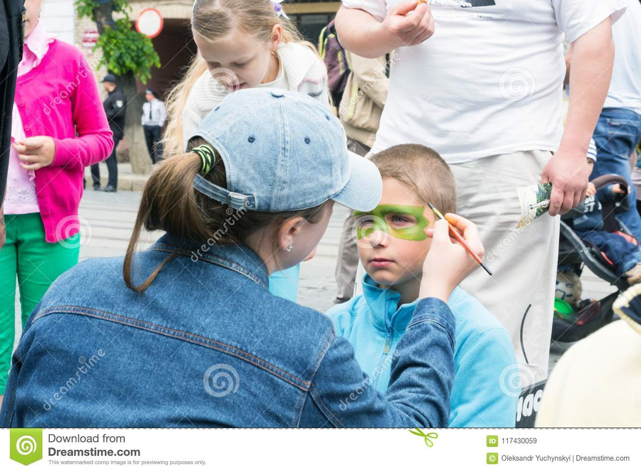 a woman paints the boy`s face with colors, during the celebration of Europe Day