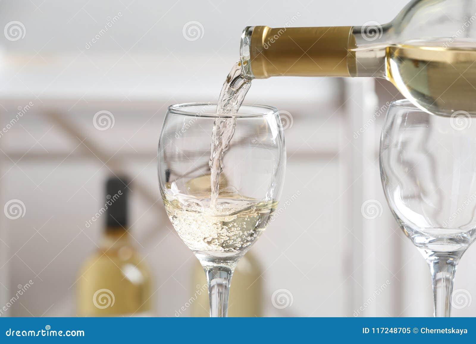 Vino blanco delicioso de colada en el vidrio