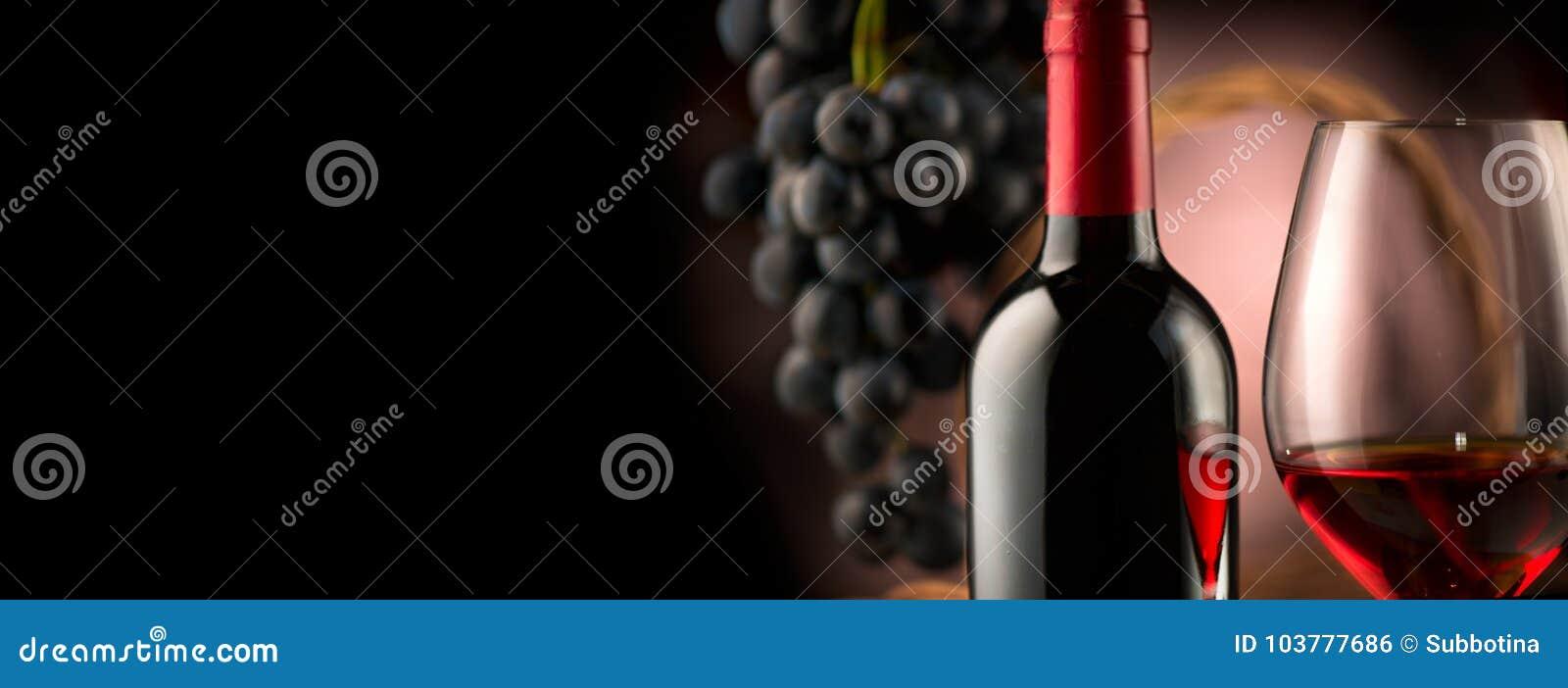Vino Botella y vidrio de vino rojo con las uvas maduras