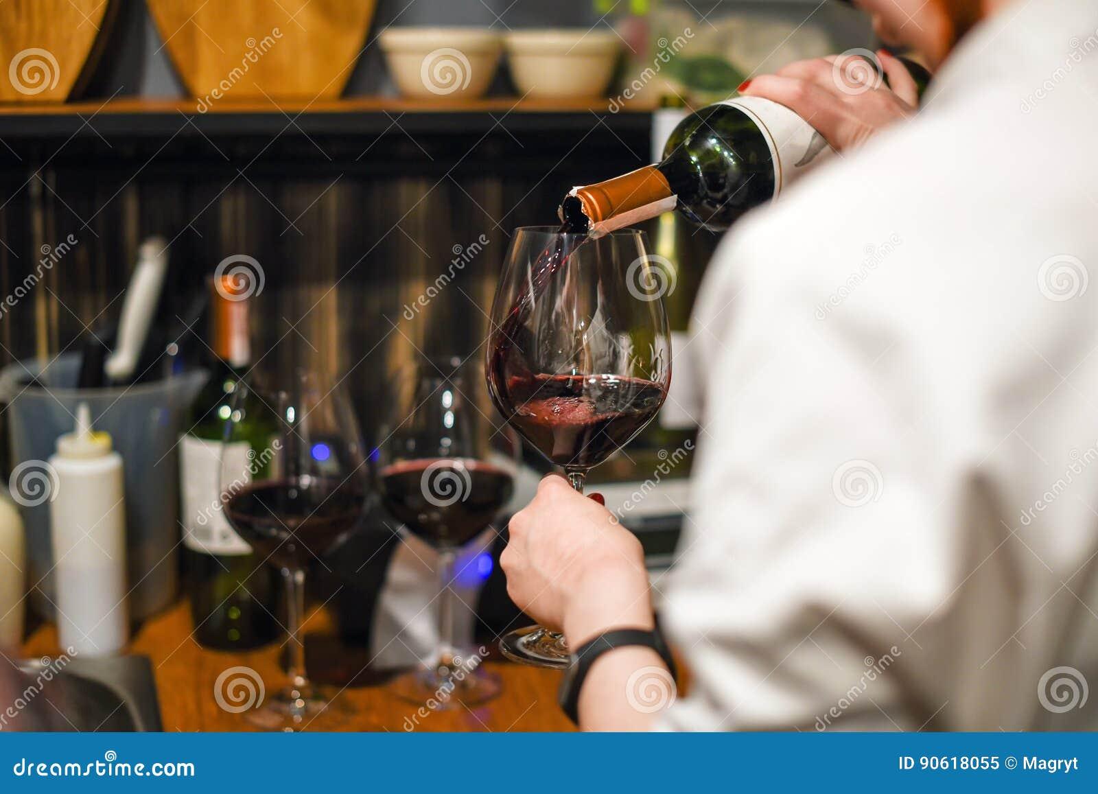 Vino de colada del camarero Sommelier experto que vierte el vino rojo en el vidrio Mujer que sostiene la botella y la copa que se