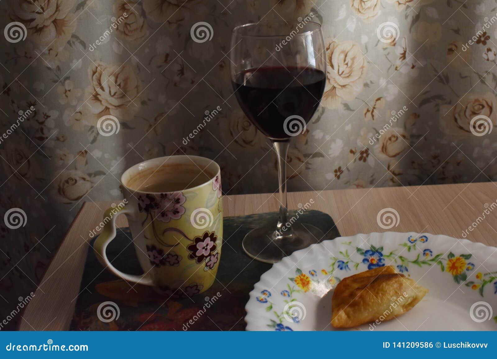 Vino domestico nel vetro con una torta mangiata per metà