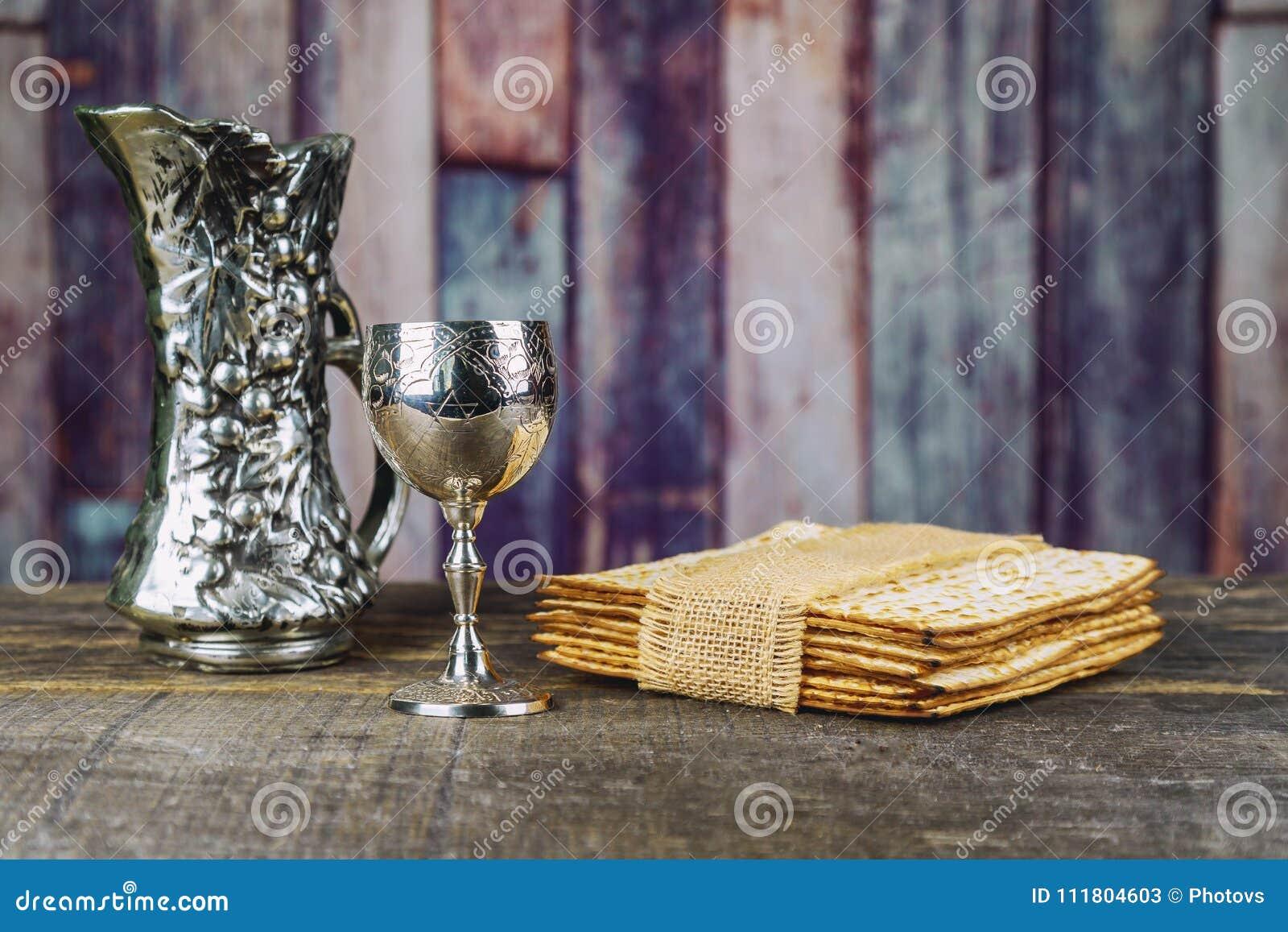Vino kosher rojo con una placa blanca del matzah o matza y un Haggadah de la pascua judía
