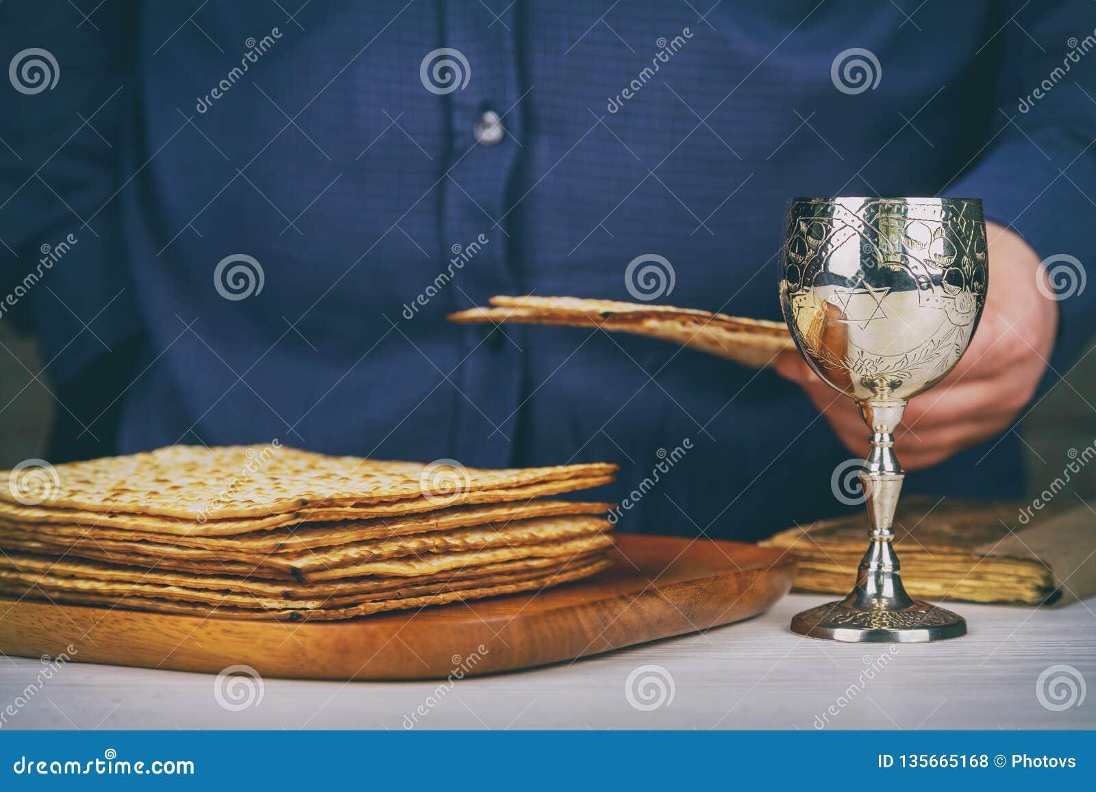 Vino kosher rojo con una placa blanca del matzah o matza y un Haggadah de la pascua judía en un fondo de madera del vintage prese