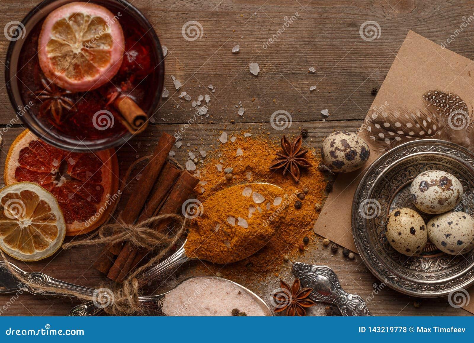 Vino reflexionado sobre, especias y frutas secadas en una tabla rústica