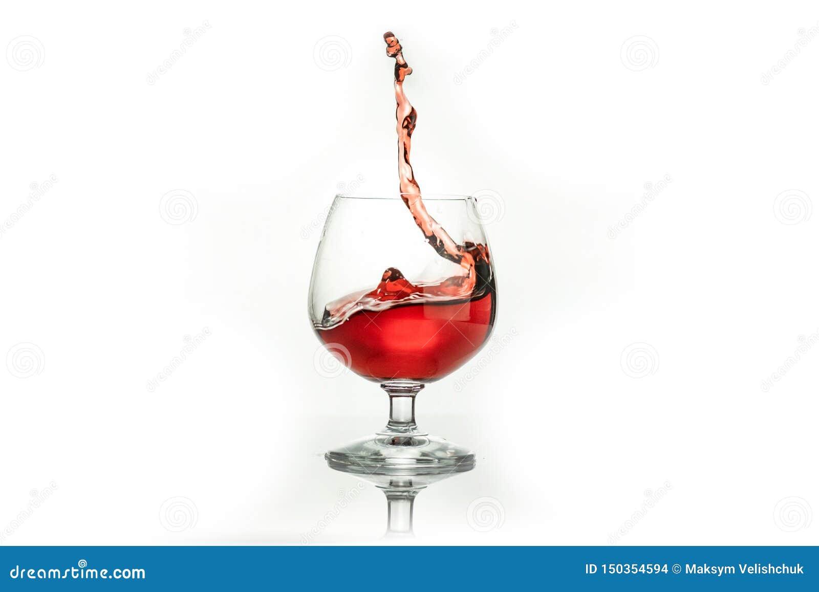 Vino rojo que salpica fuera de un vidrio, aislado en blanco