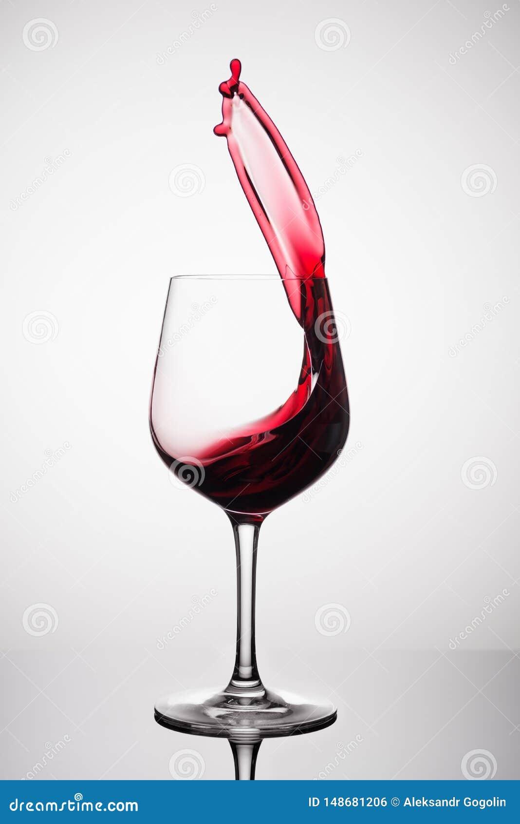 Vino rojo que salpica fuera de un vidrio