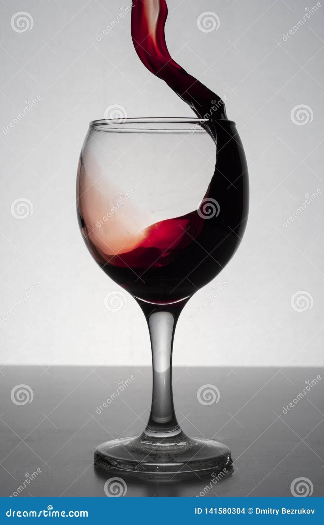 Vino rojo que salpica fuera de una copa